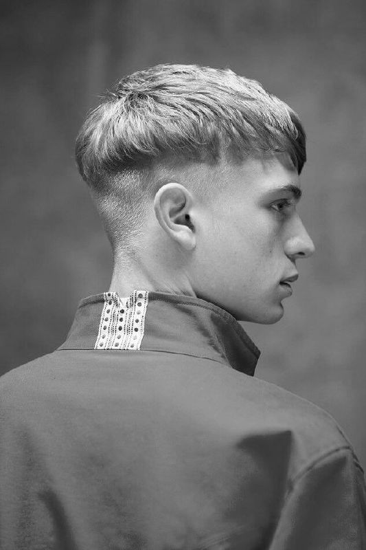 Bowl cut with a light side sweep and under shaved sides