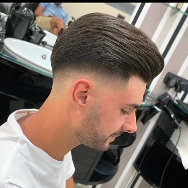 Low fade with slicked back hair