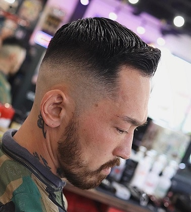 Short wavy comb over low fade hairstyle